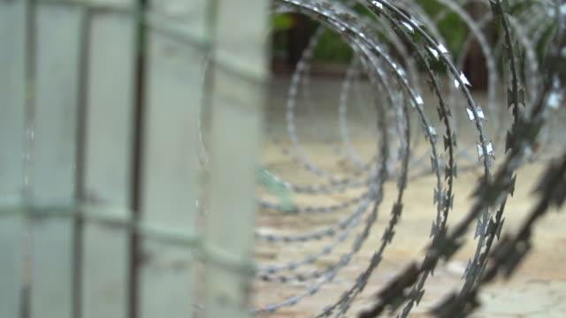 vídeos y material grabado en eventos de stock de alambre de púas de la cerca. cerca de la prisión - valla límite
