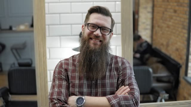 Barber and his happy customer in barbershop. Grooming the beard. Hairdressers in the workplace. Beard hairstyling and haircutting in a barber shop. video