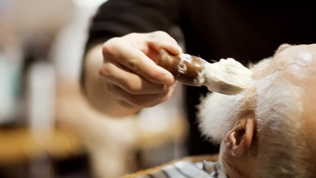 Barber applies shaving cream on face of old man and prepares skin to shaving video