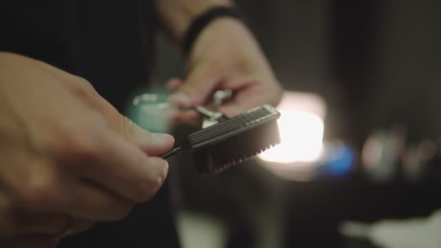 Barber cleans scissors for the next client. Care of tools for haircut, shaving. Handheld shot. 4K Barber cleans scissors for the next client. Care of tools for haircut, shaving beauty salon stock videos & royalty-free footage