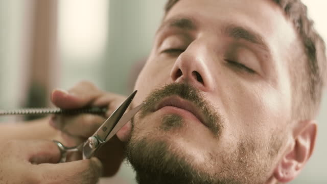 barber cut a client's mustache with clippers - baffo peluria del viso video stock e b–roll