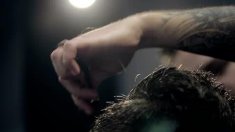 vidéos et rushes de coiffeur coupe les cheveux au salon de coiffure pour hommes.   ralenti. - coiffure