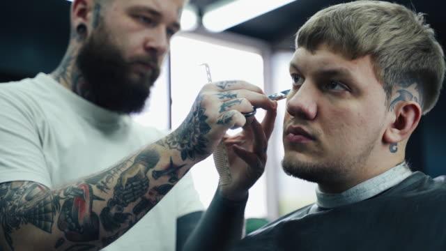 vidéos et rushes de barber coupe les cheveux du client avec des ciseaux. fermez-vous vers le haut. le mâle attirant obtient une coupe de cheveux moderne dans le salon de coiffure. tir de poche. 4k - salons et coiffeurs
