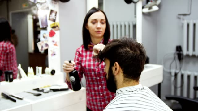 Barber cuts the hair of the client with scissors video