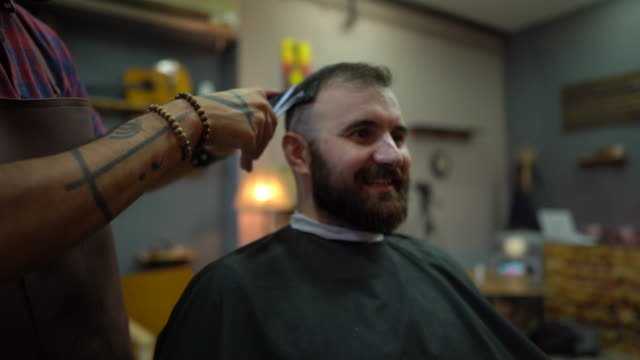 Barber cutting a client's hair in barber shop