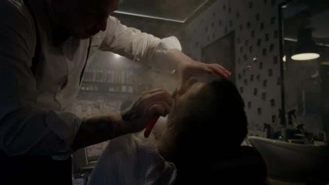 Friseur schneiden Client Bart mit Rasiermesser in Barbershop-Slow-motion – Video