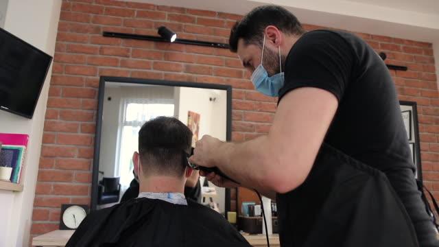 stockvideo's en b-roll-footage met kapper die het haar van de klant bij kapperswinkel knipt - mirror mask