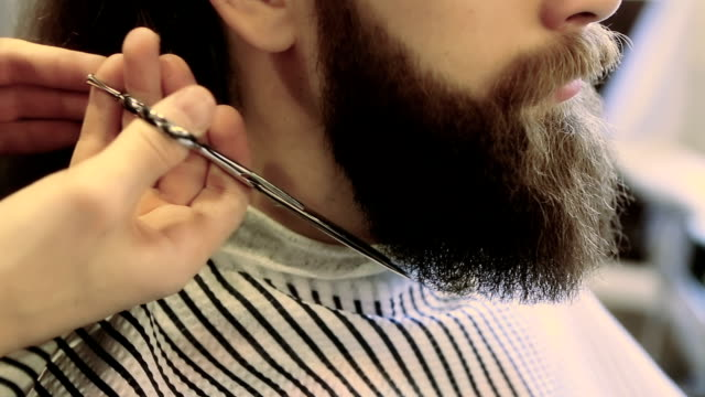 Barber cutting hair with a pair of scissors at a barber shop video
