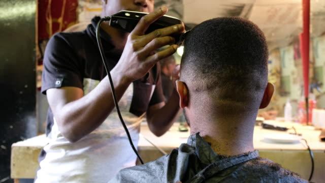 Barber cutting his clients hair with a hair clipper video