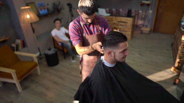 Barber cutting man's hair at barber shop