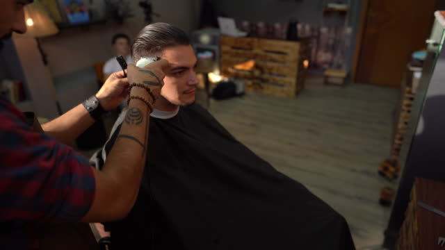 Barber cutting man's hair with hair clipper in hair salon