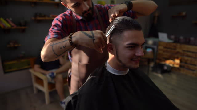 Barber cutting man's hair with scissors at barber shop