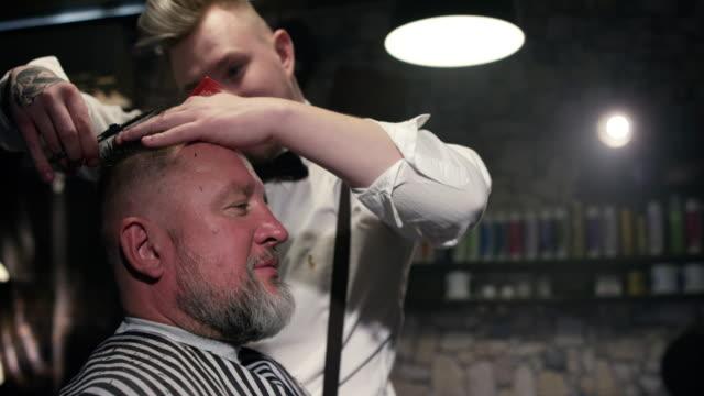 Barbier von älteren männlichen Kunden Haare schneiden mit der Schere im Barbershop-Slow-motion – Video