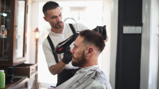 Barber drying hair to his client