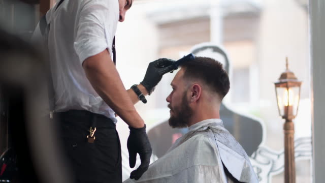 Barber giving a haircut in his barber shop Barber giving a haircut in his shop hairstyle stock videos & royalty-free footage