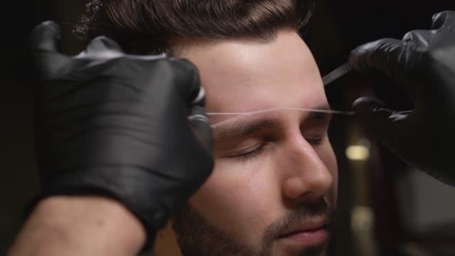 vídeos de stock e filmes b-roll de barber in black gloves doing threading procedure for client - sobrancelha