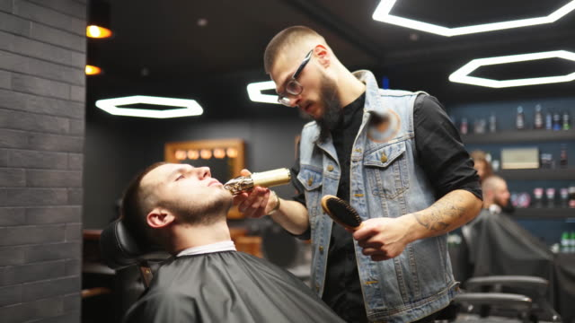 vidéos et rushes de le barbier dans des verres coupe la barbe d'homme avec un tailleur dans le salon de coiffure. coiffure et coupe de cheveux dans le salon. grooming les cheveux avec une tondeuse. coiffeur hipster faisant la coupe de cheveux dans le salon de coiffure rétr - coiffeur