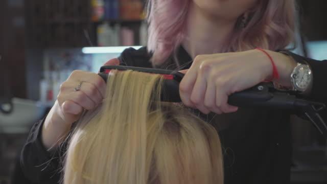 barber makes a ripple on the hair at the roots to add volume hairstyle - kosmetyczka praca w salonie piękności filmów i materiałów b-roll