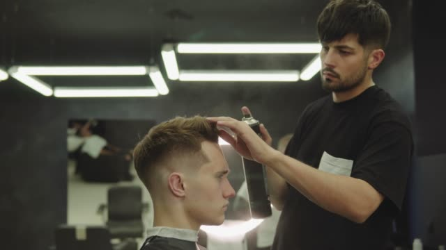 Barber makes hair styling with hair spray after haircut at the barber shop. Young handsome Caucasian man getting a haircut in a modern hairsalon. Handheld shot. 4K