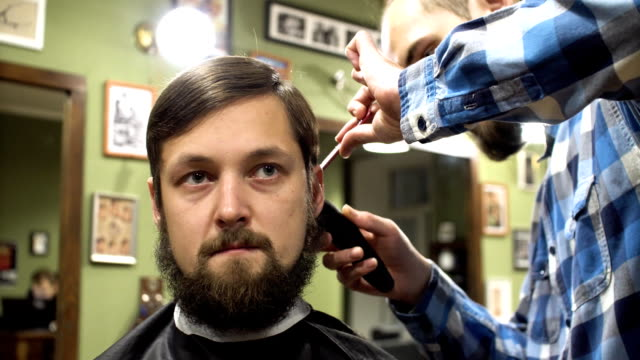 Barber making haircut of attractive bearded man in barbershop video