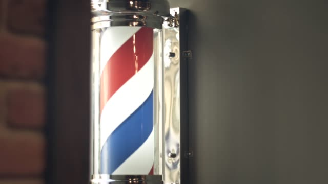 Barber pole rotating on the wall in hairdresser shop. Barber logo video