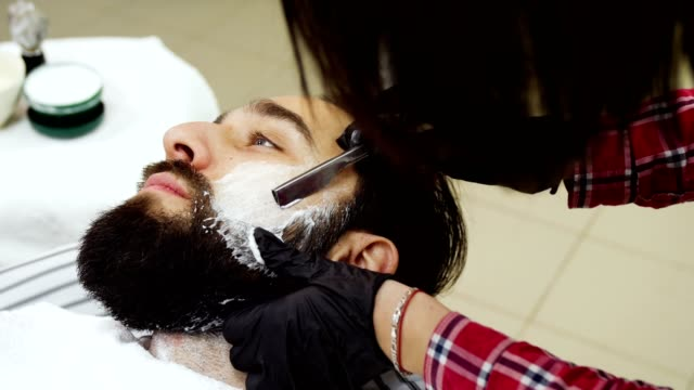 Barber shaves a white man with a straight razor video