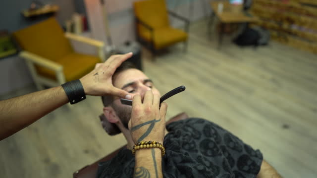 Barber shaving man's beard with straight edge razor at barber shop