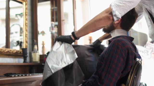 Barber spreading cape on customer in salon