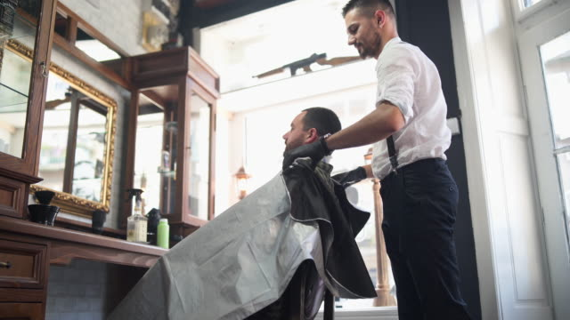 Barber spreading cape on customer in salon