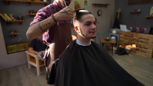 Barber styling man's hair in barber shop
