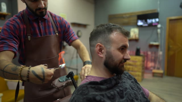 Barber trimming man's hair burning it by fire at barber shop