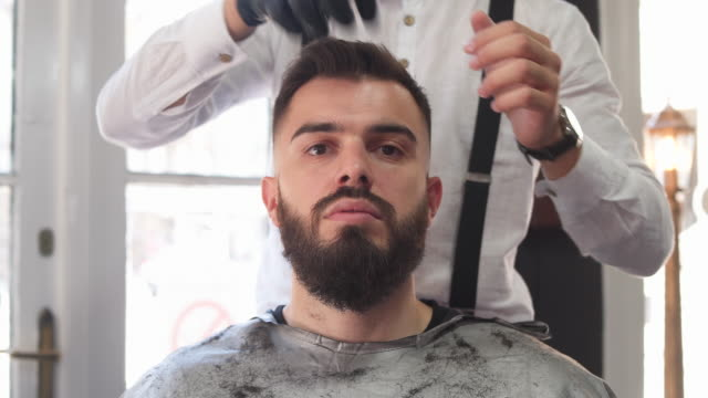 Barber using hair product to style client hair