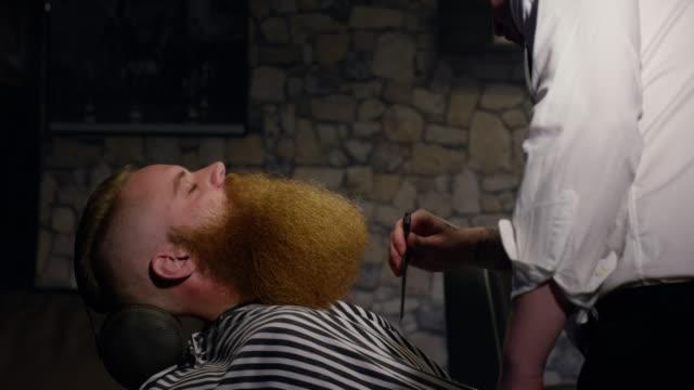 vídeos y material grabado en eventos de stock de peluquero con peine cliente hombre de larga barba en cámara lenta de barbería - largo longitud