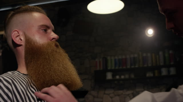 barber with comb long beard male client in barbershop slow motion - lungo video stock e b–roll