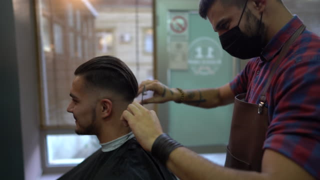 vídeos de stock e filmes b-roll de barber with protective face mask cutting a client's hair in barber shop - covid hair