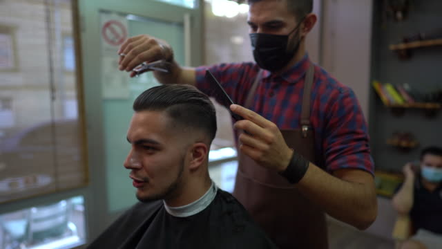 Barber with protective face mask cutting man's hair at barber shop
