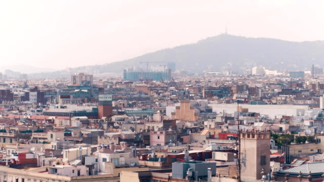 Barcelona rooftops and distant mountains, Spain. FullHD long focus pan shot video