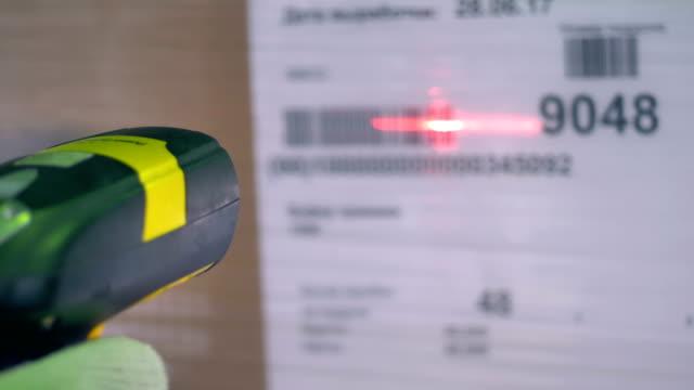 Un escáner de código de barras utilizado en una etiqueta de caja de cartón. - vídeo