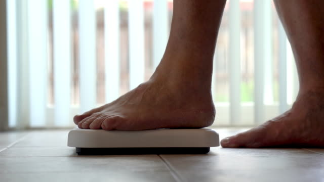 Bare feet and legs of a woman stepping onto a bathroom scale to check her weight