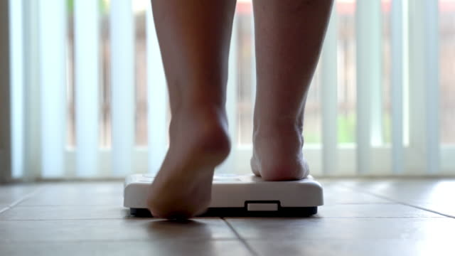 Bare feet and legs of a woman stepping onto a bathroom scale to check her weight Bare feet and legs of a woman stepping onto a bathroom scale to check her weight stepping stock videos & royalty-free footage