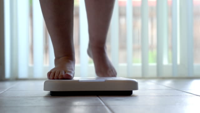 bare feet and legs of a woman stepping onto a bathroom scale to check her weight - fare un passo video stock e b–roll