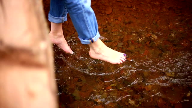 Bare feet of a woman. river water video