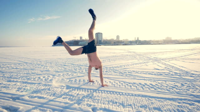 A bare-chested man does a cart-wheel motion on the snow. video