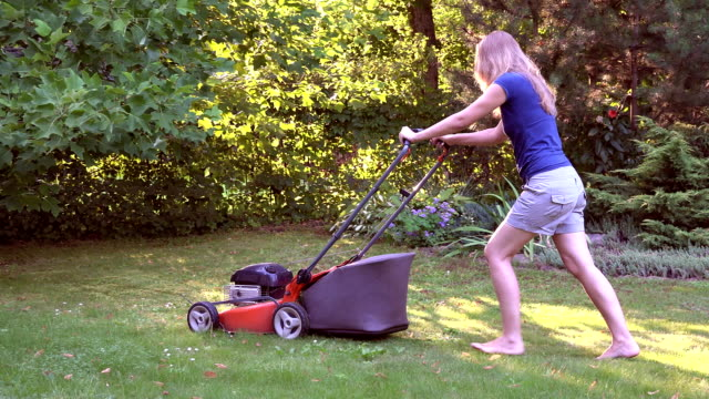 Barefeet girl woman working in garden cutting grass with lawn mower. FullHD video