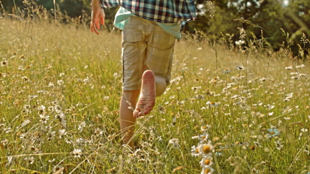 SLO MO TS Barefoot boy running in high grass video