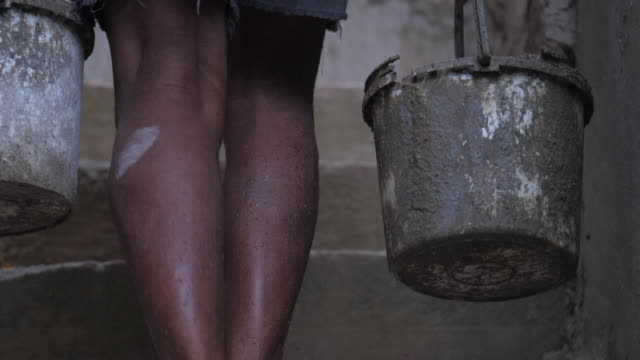 barefoot local worker carries old buckets with wet cement