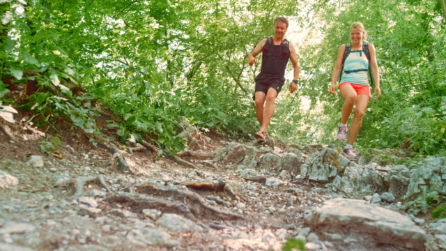 SLO MO Barefoot man and female runner going down trail