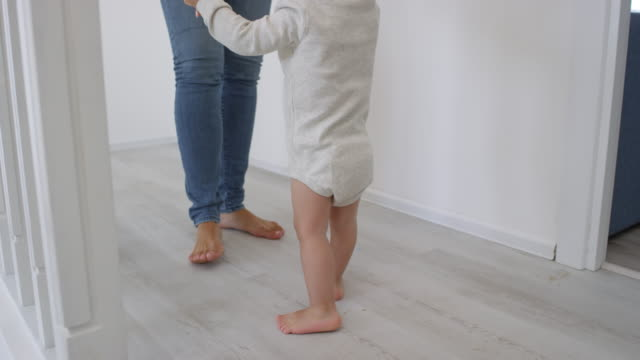 vídeos de stock e filmes b-roll de barefoot toddler learning to walk with support - feet hand