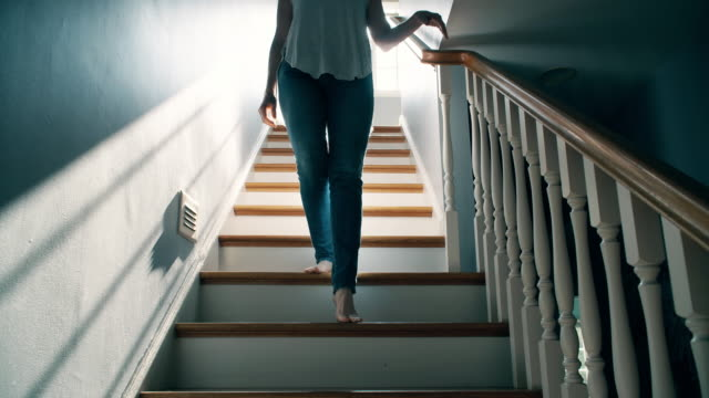 barefoot woman going down a staircase - scendere video stock e b–roll