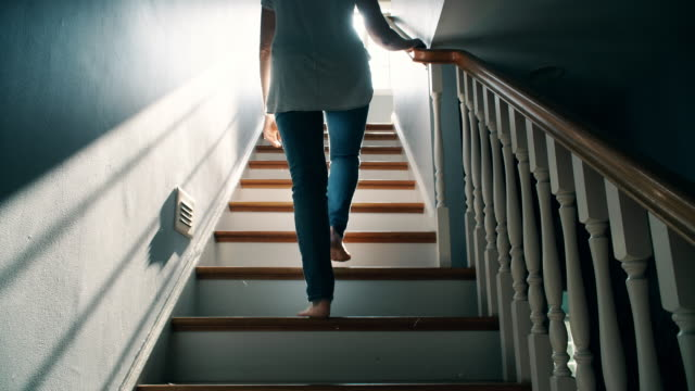 Barefoot Woman Going Up a Staircase Rear view of a back lit, barefoot late forties female in jeans going up a traditional set of stairs. moving up stock videos & royalty-free footage